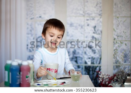 Cute little preschool boy, drawing picture on mug for his fathers birthday at home, wintertime - stock photo