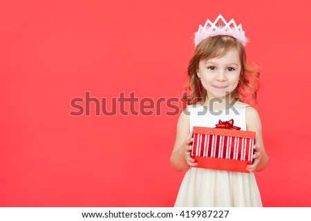 Cute little preschooler girl christmas portrait, isolated on red. Child girl wearing crown and white dress holding a red gift box  isolated over red background - stock photo