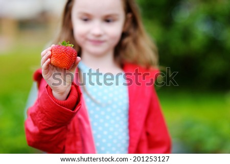 Cute little preschooler girl holding a ripe strawberry on beautiful autumn day - stock photo