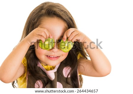 Cute little preschooler girl holding kiwi slices in front of her eyes isolated on white - stock photo