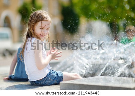 Cute little preschooler girl playing with a city fountain on hot and sunny summer day - stock photo
