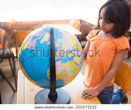 Cute little pupil looking at globe in classroom at the elementary school - stock photo