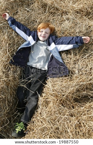 Cute little Red haired boy playing in the Hay. - stock photo