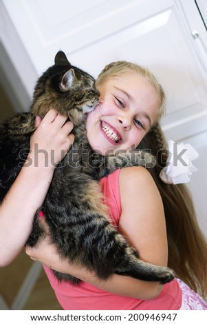 cute little school girl hugging her cat close up portrait - stock photo