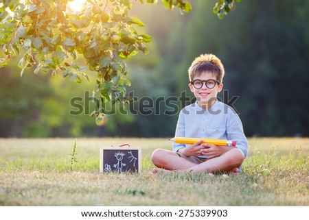 Cute little schoolboy feeling extremely excited about going back to school - stock photo