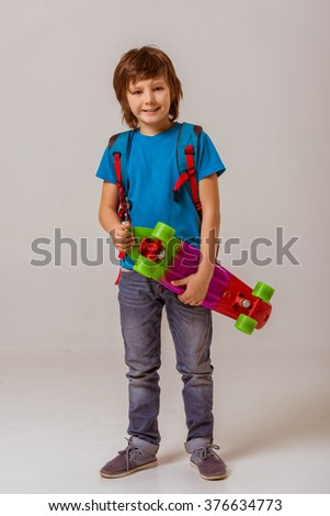 Cute little schoolboy in a blue t-shirt with a backpack holding a skateboard, looking in camera and smiling while standing on a gray background - stock photo