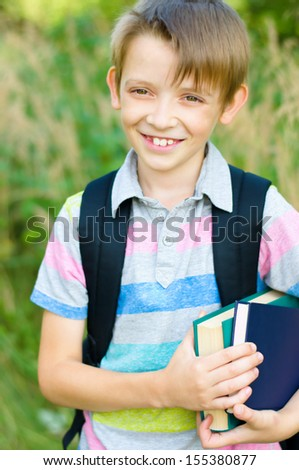 cute little schoolboy with backpack and books, outdoors - stock photo