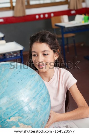 Cute little schoolgirl smiling while searching places on globe at desk in classroom - stock photo