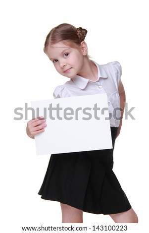 Cute little schoolgirl with lovely hairstyle posing with paper blank with empty space on Education concept theme/Gorgeous schoolgirl wearing white blouse and black skirt and holding paper blank - stock photo