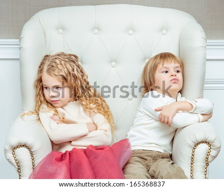 Cute little siblings (boy and girl) being at odds with each other, sitting on armchair - stock photo