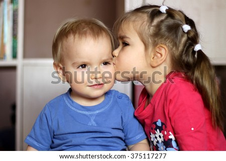 Cute little sister kissing her toddler brother with tenderness, indoor portrait, love and romantic concept - stock photo