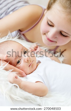 cute little sister looks at newborn on a white background - stock photo