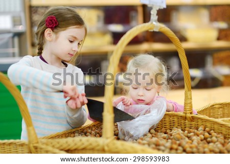 Cute little sisters buying hazelnuts in a food store or a supermarket - stock photo