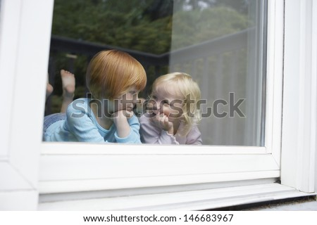 Cute little sisters looking at each other while lying in front of glass window at home - stock photo