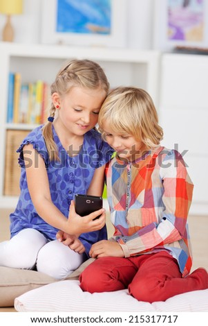Cute little sisters taking self portrait through mobile phone at home - stock photo