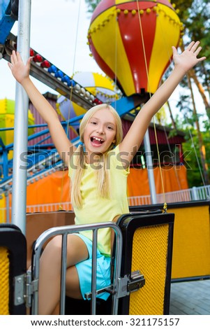 Cute little smiling girl riding a Carnival Carousel at summer theme park - stock photo