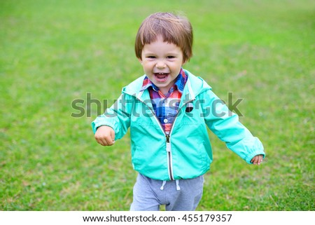 Cute little smiling toddler boy in green jacket and colored checkered shirt running in summer park, child playing on fresh green grass. Happy childhood, family weekend, holidays - stock photo