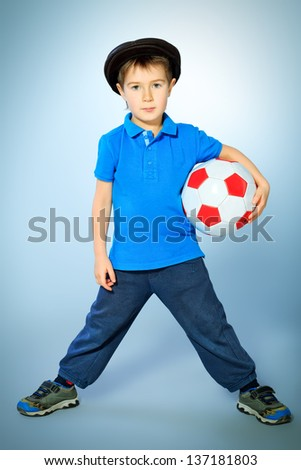 Cute little soccer player  standing with his ball. Studio shot. - stock photo