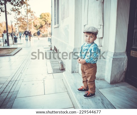 cute little stylish boy in classic style in the city in cap - stock photo