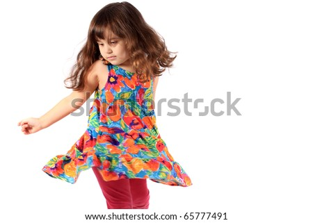 Cute little three year old girl in a flower dress dancing on a white background - stock photo