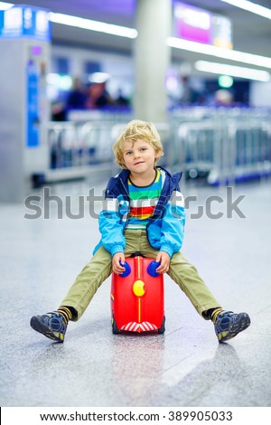 Cute little tired kid boy at the airport, traveling. Upset child waiting with kids suitcase. Canceled flight due to pilot strike. - stock photo