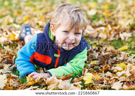 Cute little toddler child having fun with autumn foliage and leafs and lying on the ground in colorful clothes in fall park - stock photo