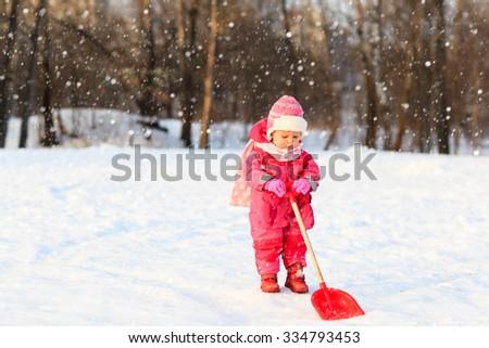 cute little toddler girl dig in winter snow, kids winter fun - stock photo