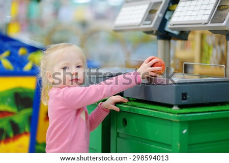 Cute little toddler girl shopping in a food store or a supermarket - stock photo