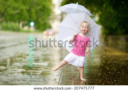 Cute little toddler girl standing in a puddle holding umbrella on a rainy summer day - stock photo