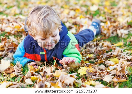 Cute little toddler kid boy having fun with autumn foliage and leafs and lying on the ground in colorful clothes in fall park - stock photo