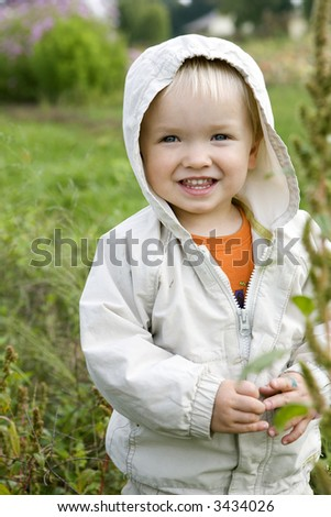 Cute little toddler with big smile on his face outdoors - stock photo