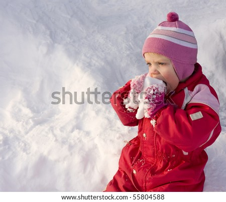Cute little toddler (2 years old) eating snow. - stock photo