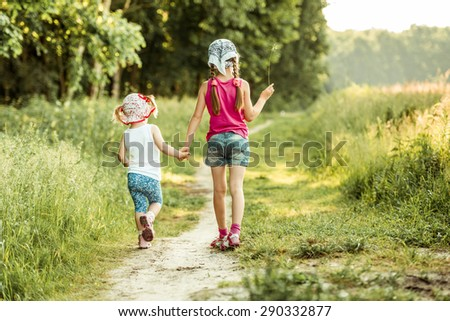Cute littles girl on the forest in summer day. back view - stock photo