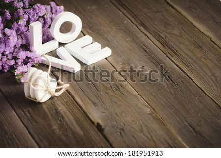 Cute love words, hearts and flowers on rustic wooden table for copy space. - stock photo