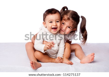 Cute lovely toddler sister hugging happy baby brother while sitting, family concept, on white. - stock photo