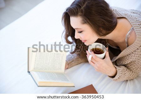 Cute lovely young woman reading book and drinking coffee on bed - stock photo
