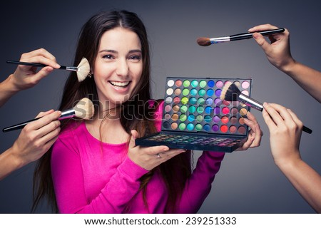Cute make-up artist holding her vast palette of colors and hands with brushes around her (color toned image) - stock photo