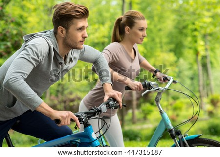 Cute man and woman riding bikes in park - stock photo