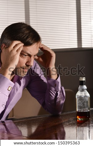 Cute  man drinks whiskey at table - stock photo