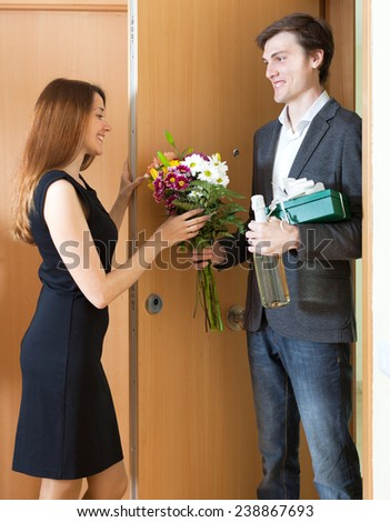 Cute man giving gifts to woman at home door - stock photo