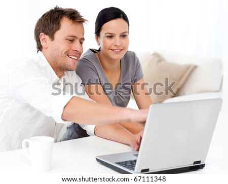 Cute man showing something on the laptop screen to his girlfriend in the living room - stock photo