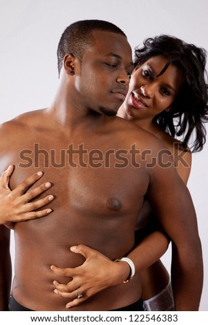 Cute married couple in sexual foreplay together in their underwear standing with her behind him and holding his chest and abdomen passionately - stock photo