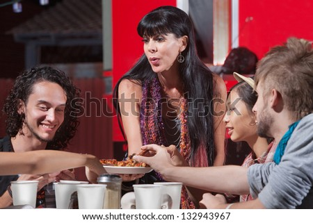 Cute mature woman sharing pizza with young group - stock photo