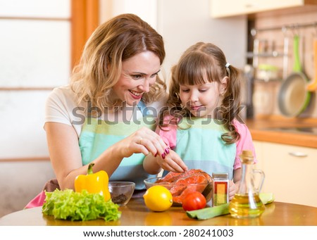 Cute middle-aged woman with child daughter preparing fish in kitchen - stock photo