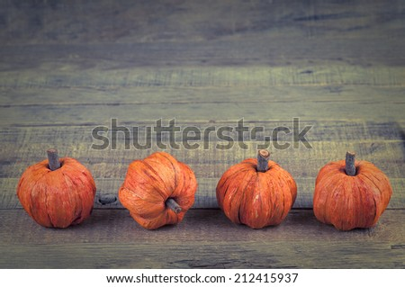 Cute Mini Pumpkins made of fibers in row at bottom of rustic wood board background with room or space for copy, text, your words.  Horizontal with instagram treatment - stock photo