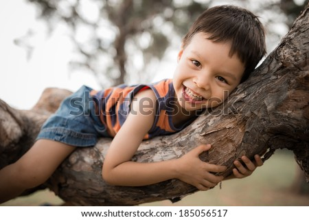 Cute mixed race Asian Caucasian boy happily lying in a tree hugging a big branch - stock photo