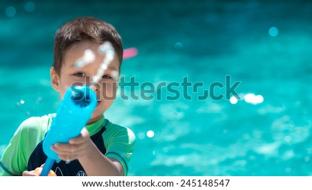 Cute mixed race Asian Caucasian boy happily plays with a water gun in a backyard swimming pool in the summer sun - stock photo