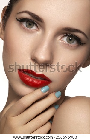 Cute model face with bright classical evening make-up, eyeliner on eyes, red lipstick, purity skin on white background. Bright mint nail polish on her nails - stock photo