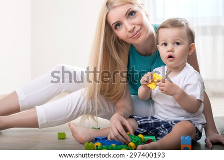 Cute mom is playing with her baby. They are holding toys and sitting on floor. The family is looking forward with interest. The woman is gently smiling - stock photo