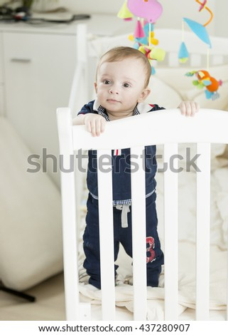 Cute 9 month old baby boy standing in white wooden crib - stock photo